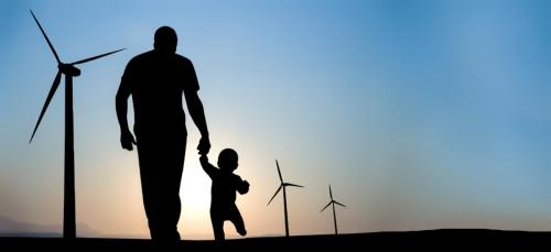 energy-renewable-man-and-baby-walking-toward-wind-turbines