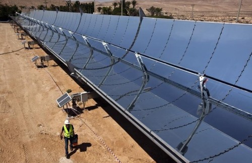 A worker walks next to parabolic mirrors at the research site of solar power company Brenmiller Energy near Dimona